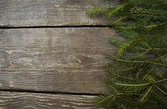 Το φωτεινό πλαίσιο υποβάθρου Χριστουγέννων με ένα διάστημα αντιγράφων με το έλατο διακλαδίζεται με έναν ξύλινο πίνακα στοκ φωτογραφία