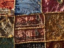 Το φωτεινό υπόβαθρο ενός coverlet υφασμάτων είναι κόκκινα, καφετιά και μπλε τετράγωνα με ένα σχέδιο ανακούφισης της διακόσμησης Στοκ φωτογραφία με δικαίωμα ελεύθερης χρήσης