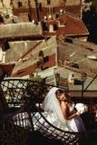 Το φόρεμα νυφών ` s βρίσκεται στα σπειροειδή σκαλοπάτια ενώ απολαμβάνει sunshin Στοκ Εικόνες