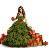 Το φόρεμα χριστουγεννιάτικων δέντρων γυναικών και παρουσιάζει τα δώρα, νέα μόδα έτους Στοκ φωτογραφία με δικαίωμα ελεύθερης χρήσης
