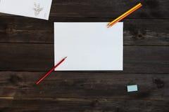Το φύλλο και τα μολύβια λευκωμάτων βρίσκονται σε έναν πίνακα του ξύλου Στοκ Φωτογραφία