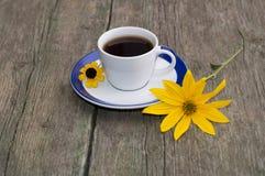 Το φλιτζάνι του καφέ σε έναν ξύλινο πίνακα που διακοσμείται με δύο κίτρινα ΛΦ Στοκ Εικόνα