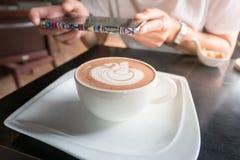 Το φλιτζάνι του καφέ σε έναν πίνακα στον καφέ με το θηλυκό θαμπάδων παίρνει ένα υπόβαθρο φωτογραφιών Τρύγος fillter Στοκ Εικόνες