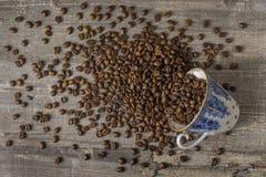 Το φλυτζάνι καφέ ανατρέπει τον ξύλινο πίνακα φασολιών μια σκοτεινή ανασκόπηση μπλε σχέδιο Στοκ Εικόνες