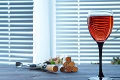 Το φλυτζάνι του ρόδινου κρασιού στον πίνακα με το ανοιχτήρι και βουλώνει Στοκ Φωτογραφία