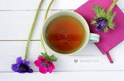 Το φλυτζάνι του τσαγιού και τα λουλούδια με το ρόδινο σημειωματάριο και σας ευχαριστούν Στοκ Εικόνες