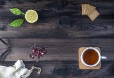 Το φλυτζάνι του τσαγιού με τα μπισκότα τσαγιού, φρέσκα hibiscus λεμονιών τοποθετεί σε σάκκο στον ξύλινο πίνακα Στοκ εικόνα με δικαίωμα ελεύθερης χρήσης