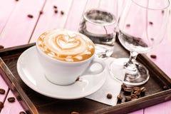 Το φλυτζάνι του cappuccino με τον αφρό καρδιών, σύνολο φλιτζανιού του καφέ με τα φασόλια καφέ στο ρόδινο ξύλινο υπόβαθρο, πίνει τ Στοκ Φωτογραφίες