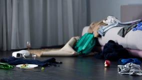 Το χάος και βρωμίζει στο δωμάτιο μετά από το κόμμα, το ύφασμα και τα τρόφιμα στο πάτωμα, διαμέρισμα αγάμων Στοκ Φωτογραφίες