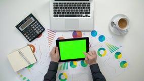 Το χέρια ατόμων ` s που κρατούν ένα ι-μαξιλάρι με μια πράσινη οθόνη Στοκ Φωτογραφίες