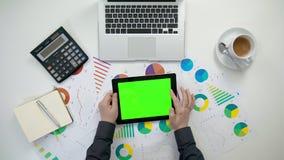 Το χέρια ατόμων ` s που κρατούν ένα ι-μαξιλάρι με μια πράσινη οθόνη Στοκ Εικόνες