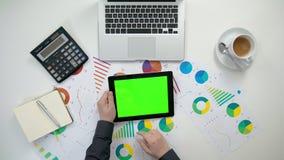 Το χέρια ατόμων ` s που κρατούν ένα ι-μαξιλάρι με μια πράσινη οθόνη Στοκ Εικόνα