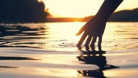 Το χέρι αγγίζει ήπια την επιφάνεια του νερού στη λίμνη στο χρυσό ηλιοβασίλεμα απόθεμα βίντεο