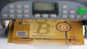 Το χέρι ανάβει τη μετρώντας μηχανή μετρητών Bitcoin φιλμ μικρού μήκους