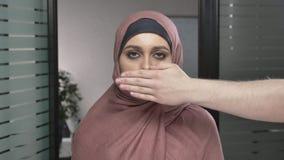 Το χέρι ανδρών ` s καλύπτει ένα στόμα γυναικών ` s Αραβική γυναίκα στο ρόδινο hijab Πρόβλημα, παράβαση, φοβέρα εξετάζει τη κάμερα απόθεμα βίντεο