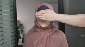 Το χέρι ανδρών ` s καλύπτει το τα μάτια γυναικών ` s Αραβική γυναίκα στο ρόδινο hijab Πρόβλημα, παράβαση, φοβέρα εξετάζει τη κάμε απόθεμα βίντεο