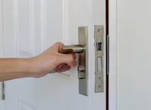 Το χέρι ανοίγει την πόρτα, άσπρη πόρτα Στοκ εικόνες με δικαίωμα ελεύθερης χρήσης