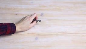 Το χέρι ανυψώνει ένα κλειδί μετάλλων από έναν ξύλινο πίνακα φιλμ μικρού μήκους