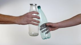 Το χέρι αρνείται το πλαστικό μπουκάλι υπέρ του επαναχρησιμοποιήσιμου μπουκαλιού γυαλιού, πλαστική ρύπανση απόθεμα βίντεο