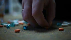 Το χέρι αρπάζει ένα χάπι συνταγών από το βρώμικο πάτωμα - έννοια εθισμού στα ναρκωτικά απόθεμα βίντεο