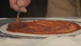 Το χέρι αρχιμαγείρων διαδίδει τον παστεριωμένο τοματοπολτό επάνω σε μια βάση πιτσών απόθεμα βίντεο