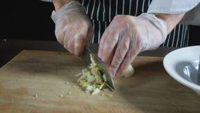 Το χέρι αρχιμαγείρων κόβει το σκληρό βρασμένο αυγό φιλμ μικρού μήκους