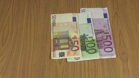 Το χέρι ατόμων έβαλε το διαφορετικό ευρο- τραπεζογραμμάτιο μετρητών χρημάτων στον πίνακα 4K φιλμ μικρού μήκους