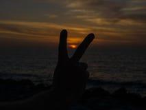 Το χέρι ατόμων που αυξάνει δύο δάχτυλα στο υπόβαθρο ηλιοβασιλέματος, ζωή πηγαίνει στην έννοια Στοκ Φωτογραφία