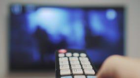 Το χέρι ατόμων που κρατά τον τηλεχειρισμό τρόπου ζωής TV και κλείνει την έξυπνη TV σερφ καναλιών Κλείστε επάνω επανδρώνει τη TV ε απόθεμα βίντεο
