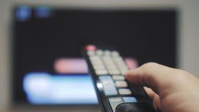 Το χέρι ατόμων που κρατά τον τηλεχειρισμό TV και κλείνει τον έξυπνο τρόπο ζωής TV σερφ καναλιών Κλείστε επάνω επανδρώνει τη TV εκ απόθεμα βίντεο