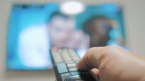 Το χέρι ατόμων που κρατά τον τηλεχειρισμό TV και κλείνει την έξυπνη TV σερφ καναλιών Κλείστε επάνω επανδρώνει τη TV εκμετάλλευσης απόθεμα βίντεο