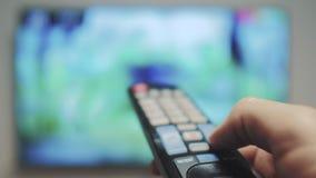 Το χέρι ατόμων που κρατά τον τηλεχειρισμό TV και κλείνει την έξυπνη TV Σερφ τρόπου ζωής καναλιών Κλείστε επάνω επανδρώνει τη TV ε απόθεμα βίντεο