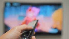 Το χέρι ατόμων που κρατά τον τηλεχειρισμό TV και κλείνει την έξυπνη TV σερφ καναλιών Κλείστε επάνω επανδρώνει τη TV εκμετάλλευσης φιλμ μικρού μήκους