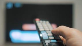 Το χέρι ατόμων που κρατά τον τηλεχειρισμό TV και κλείνει την έξυπνη TV τρόπου ζωής σερφ καναλιών Κλείστε επάνω επανδρώνει τη TV ε απόθεμα βίντεο