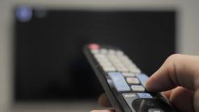 Το χέρι ατόμων που κρατούν τον τηλεχειρισμό TV και ο τρόπος ζωής κλείνουν την έξυπνη TV σερφ καναλιών Κλείστε επάνω επανδρώνει τη απόθεμα βίντεο