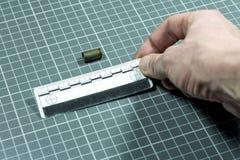 Το χέρι ατόμων ` s εφαρμόζει το δικανικό κυβερνήτη στην περίπτωση κασετών χωρίς μια σφαίρα από το πιστόλι για τη βαλλιστική εξέτα Στοκ Εικόνα