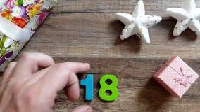Το χέρι ατόμων ` s κάνει τον αριθμό το 2018 σε έναν ξύλινο πίνακα με τις διακοσμήσεις Χριστουγέννων απόθεμα βίντεο