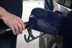 Το χέρι ατόμων ` s κρατά ένα πιστόλι καυσίμων και ανεφοδιάζει σε καύσιμα το αυτοκίνητό του με τη βενζίνη Στοκ εικόνα με δικαίωμα ελεύθερης χρήσης