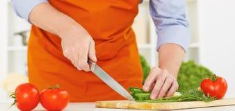Το χέρι ατόμων ` s με ένα μαχαίρι έκοψε το πράσινο κρεμμύδι Στοκ Εικόνα
