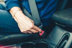 Το χέρι ατόμων ` s στερεώνει τη ζώνη ασφαλείας του αυτοκινήτου Κλείστε το κάθισμα αυτοκινήτων σας Στοκ εικόνα με δικαίωμα ελεύθερης χρήσης