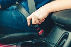 Το χέρι ατόμων ` s στερεώνει τη ζώνη ασφαλείας του αυτοκινήτου Κλείστε το κάθισμα αυτοκινήτων σας στοκ εικόνες με δικαίωμα ελεύθερης χρήσης