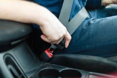 Το χέρι ατόμων ` s στερεώνει τη ζώνη ασφαλείας του αυτοκινήτου στοκ φωτογραφία με δικαίωμα ελεύθερης χρήσης