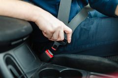 Το χέρι ατόμων ` s στερεώνει τη ζώνη ασφαλείας του αυτοκινήτου Στοκ φωτογραφίες με δικαίωμα ελεύθερης χρήσης