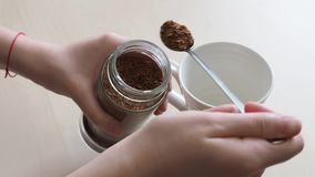 Το χέρι βάζει την κουταλιά δύο του στιγμιαίου καφέ από το βάζο γυαλιού στην κούπα απόθεμα βίντεο