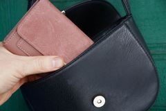 Το χέρι βγάζει ένα καφετί πορτοφόλι από μια ανοικτή μαύρη τσάντα δέρματος στοκ εικόνα