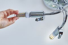 Το χέρι βιδώνει το λαμπτήρα καλαμποκιού των οδηγήσεων στον ανώτατο πολυέλαιο στοκ φωτογραφίες με δικαίωμα ελεύθερης χρήσης