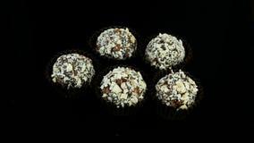 Το χέρι βιομηχανιών ζαχαρωδών προϊόντων κινηματογραφήσεων σε πρώτο πλάνο βάζει τις καραμέλες σοκολάτας στο μαύρο υπόβαθρο φιλμ μικρού μήκους