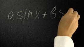 Το χέρι γράφει με μια κιμωλία έναν μαθηματικό ενός τύπου σε έναν πίνακα απόθεμα βίντεο