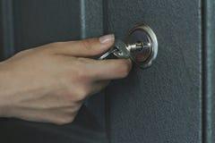 Το χέρι, γυναίκες είναι ξεκλειδωμένη πόρτα Στοκ Εικόνες