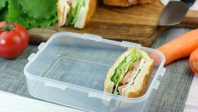 Το χέρι γυναικών έβαλε τα φρέσκα γίνοντα σάντουιτς στο καλαθάκι με φαγητό φιλμ μικρού μήκους